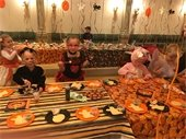 Children gathered at table, decorating cookies for Chevy Chase Village Halloween Party