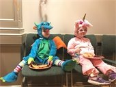 Two children sitting and eating pizza at Halloween Party