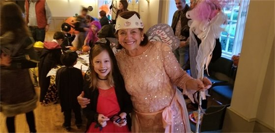 Ms. Pauly one of the CCV toddler dance instructors at the Halloween party dressed as the fairy godmother, and a little girl standing next to her dressed like the devil