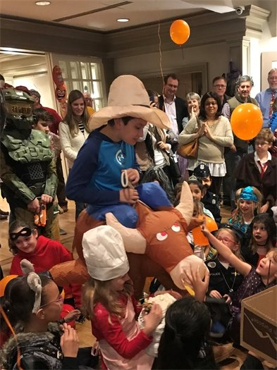 Children gathered on the floor as the boy in the cowboy costume with bull walks through