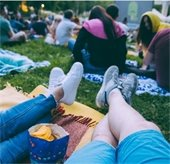 Image of people on blankets in the park for a movie