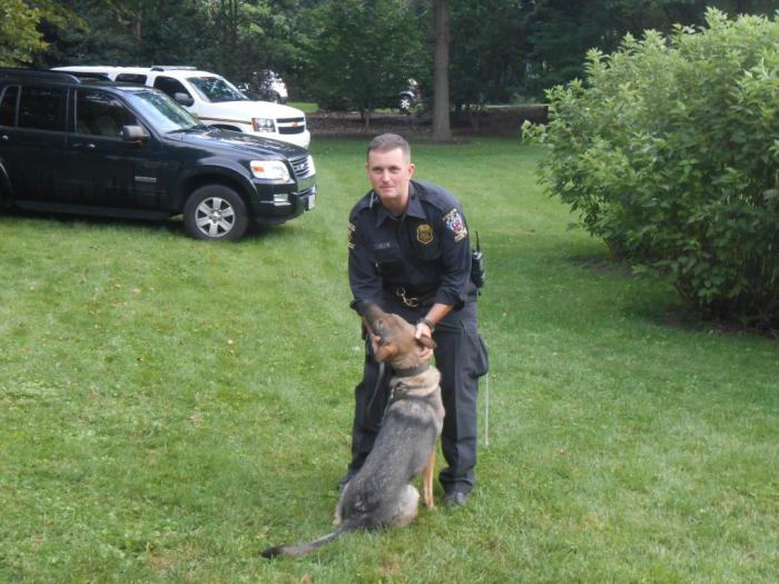 Police officer and police dog sitting