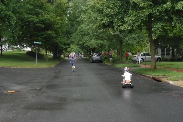 Young person riding tricycle at a distance